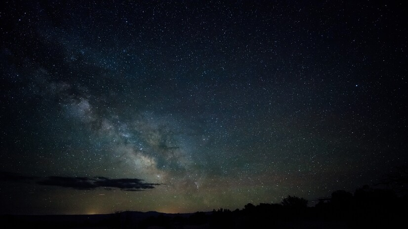 A long-exposure picture of the night sky. Thousands of stars are visible, as well as the band of the milky way.